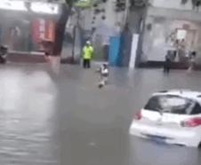 惊险!暴雨积水女子在路面游泳 结果险被卷入车底
